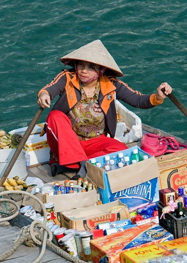 Woman rows floating supply boat with biscuits drinks cooking oil and cakes among tourist cruising boats Halong Bay Vietnam : Stock Photo