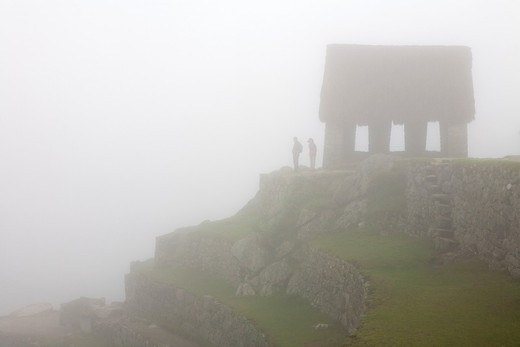 Two tourists silhouetted next to the ´Watchman´s Hut´ or ´Guard House´ on a foggy morning at Machu Picchu, Peru : Stock Photo