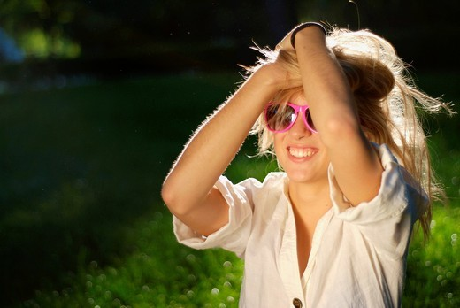 Cute young blonde woman in a park, wearing pink sunglasses : Stock Photo