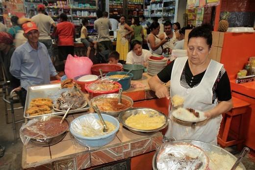 Nicaragua, Managua, Mercado Roberto Huembes, market, marketplace, shopping, vendor, stall, Hispanic, woman, man, cook, customer, traditional food, serving, plate, customer, apron, restaurant, self-employed, for sale, : Stock Photo