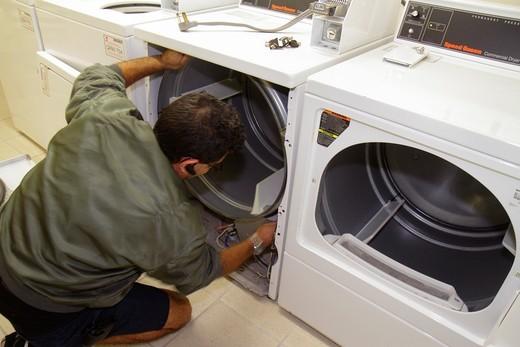 Florida, Miami Beach, ´Ocean Drive´, Presidential Condominiums, laundry room, Hispanic, man, clothes dryer, repair, repairman, replacing, parts, motor, maintenance, : Stock Photo
