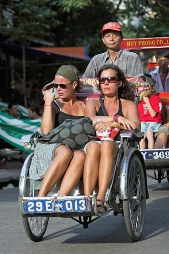 Two women tour Hanoi Old Quarter by cyclo rickshaw Vietnam : Stock Photo
