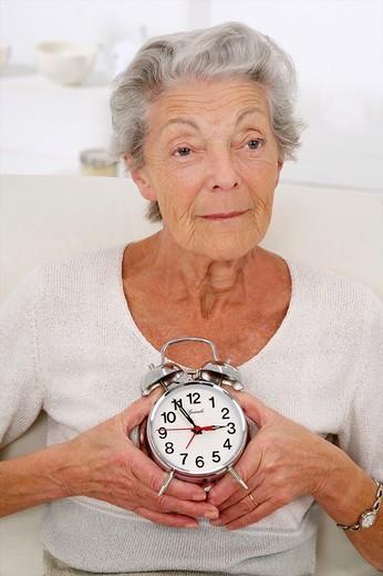 Senior woman thoughtful holding an alarm clock : Stock Photo