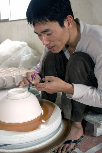 Stock Photo: 1566-916536 Craftsman paints bowl on potters wheel Bat Trang pottery village near Hanoi Vietnam