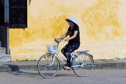 Stock Photo: 1566-916541 Conical hat woman rides bicycle Hoi An Vietnam