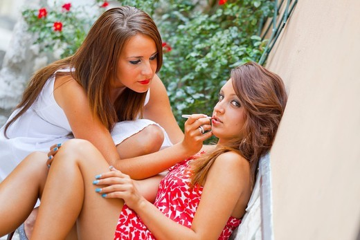 Two attractive young women appying make-up on the street : Stock Photo