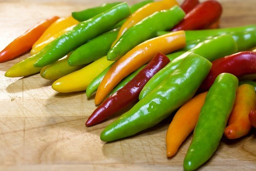 An assortment of various colors of peppers on a cutting board : Stock Photo