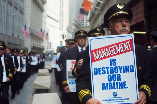 United and Continental pilots conduct an informational picket outside the New York Stock Exchange on the eve of the one-year anniversary of the corporate merger  The pilots, represented by ALPA, are protesting the pace of their collective bargaining negot. United and Continental pilots conduct an informational picket outside the New York Stock Exchange on the eve of the one-year anniversary of the corporate merger  The pilots, represented by ALPA, are protesting the pace of their collective barg : Stock Photo