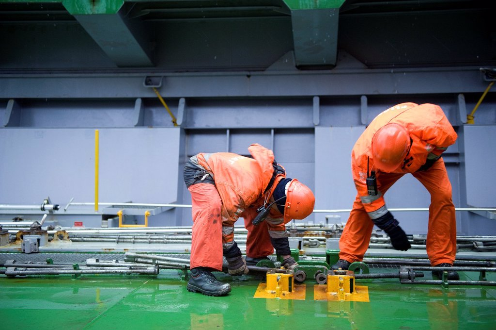 Two ´Able Seamen´ or sailors are preparing the hole and the deck of container-vessel MV Flintercape, for recieving new containers. The Flinetrcape will sail from Rotterdam, Netherlands to Sundsvall, Sweden. The men are both Indonesian men. : Stock Photo