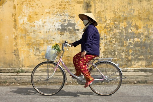 Stock Photo: 1566-920264 Conical hat woman rides bicycle with basket of flowers from market Hoi An historic town mid Vietnam