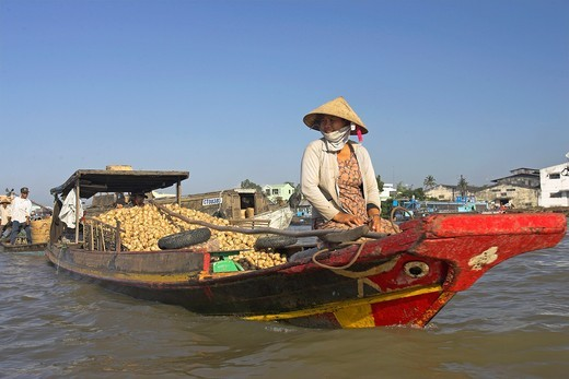 Stock Photo: 1566-920566 Woman in conical hat on painted riverboat with vegetables Cai Ran floating market near Can Tho Vietnam