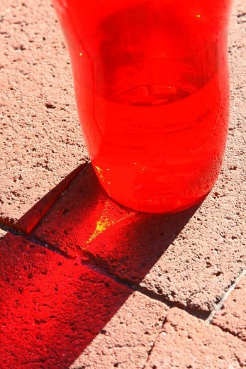 lower half of red water bottle with clear liquid inside casting red shadow, including bright streak inside shadow, on brownish-pink brick surface : Stock Photo