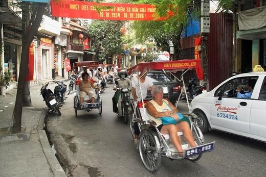 Stock Photo: 1566-922079 Visitors on cyclo rickshaw group tour of Old Quarter Ma May Street Hanoi Vietnam