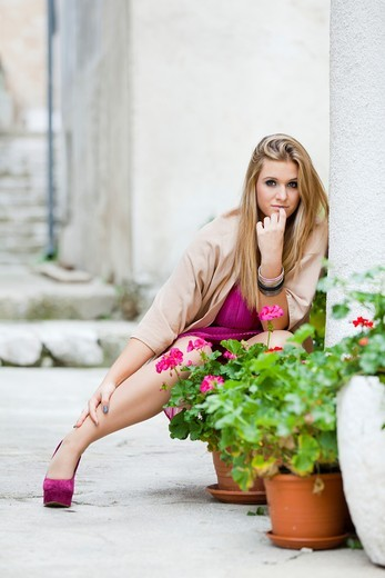 Squatting behind flowers in vases attractive young woman : Stock Photo
