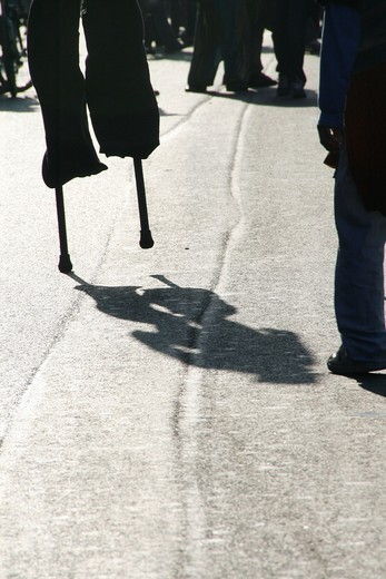 Stock Photo: 1566-922397 person man walking on stilts in street road in city town
