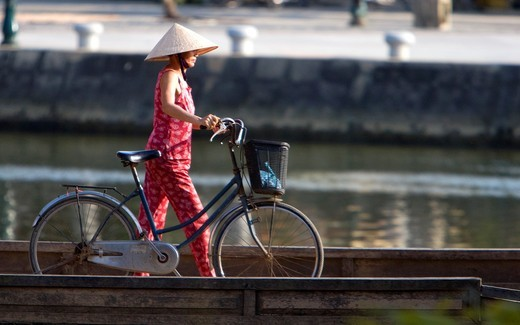 Stock Photo: 1566-923402 Conical hat woman pushes bicycle over footbridge Hoi An Vietnam