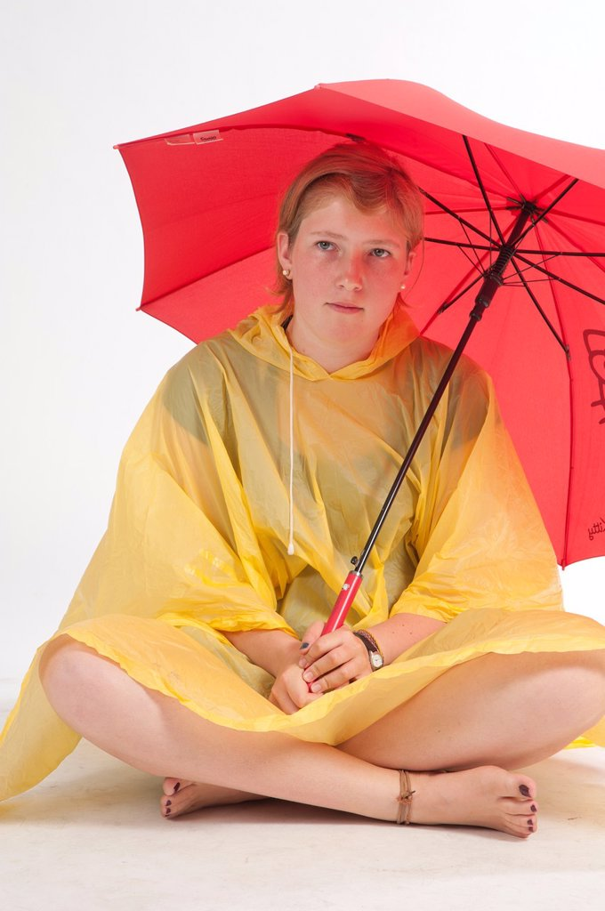 Stock Photo: 1566-924067 Teenage girl sitting on the floor with yellow rain gear protected with red umbrella.