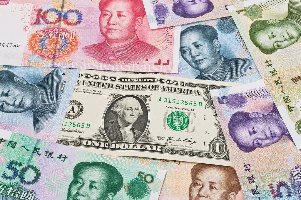 Many Yuan bills with the portrait of Mao Zedong lying side by side In the middle lies a 1 U S Dollar bill The renminbi, the Chinese currency, was introduced in 1949 after the founding of the People´s Republic of China China, Asia : Stock Photo