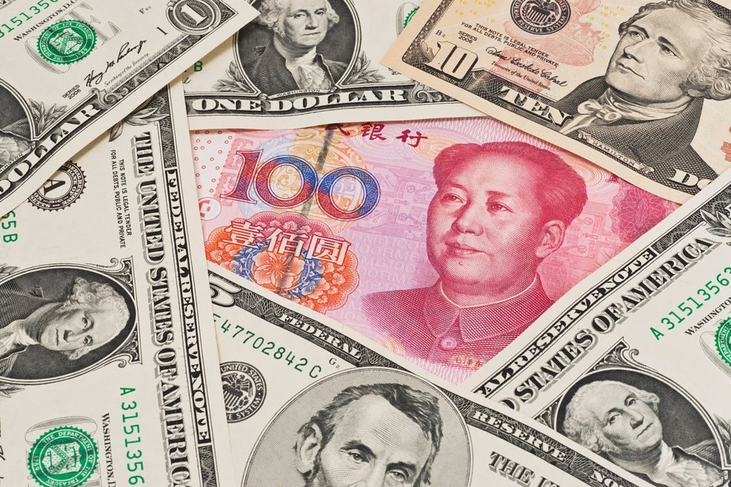 Many U S Dollar bills lying side by side In the middle lies a Chinese 100 Yuan bill with the portrait of Mao Zedong The renminbi, the Chinese currency, was introduced in 1949 after the founding of the People´s Republic of China : Stock Photo