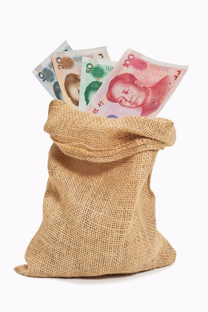 Many diverse Chinese Yuan bills with the portrait of Mao Zedong are in a jute bag The renminbi, the Chinese currency, was introduced in 1949 after the founding of the People´s Republic of China : Stock Photo