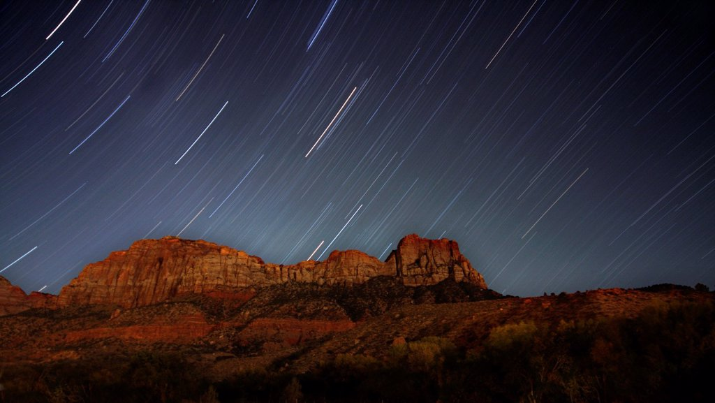 Stock Photo: 1566-924874 Star trails appear over The Watchman mountain at night at Zion National Park, Utah