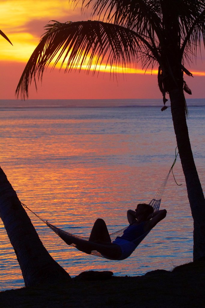 Woman in hammock, and palm trees at sunset, Coral Coast, Viti Levu, Fiji, South Pacific : Stock Photo