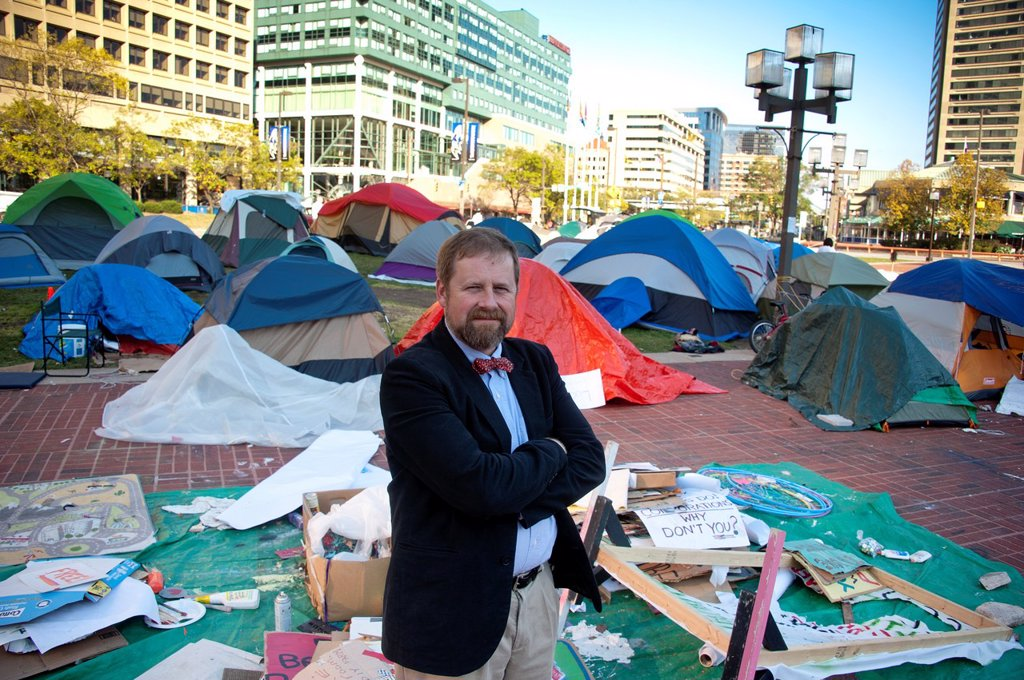 Stock Photo: 1566-925474 Man stands in jest against occupy movement tents in Baltimore Maryland USA