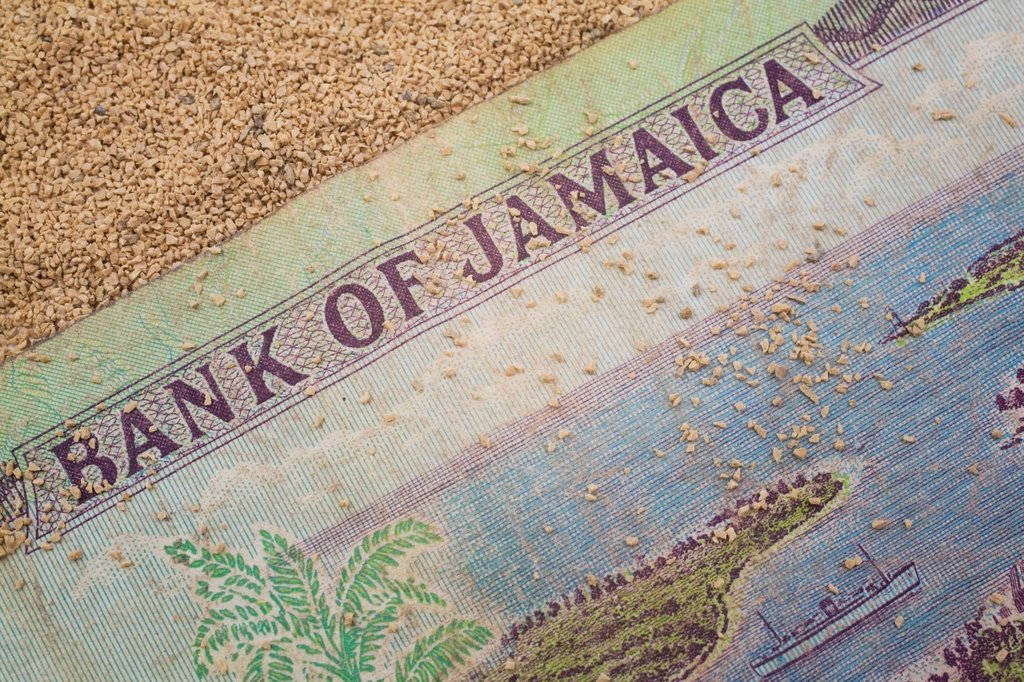 Stock Photo: 1566-926927 Close-up of a Bank of Jamaica currency bank note on a coarse-grained sand background, Studio Composition