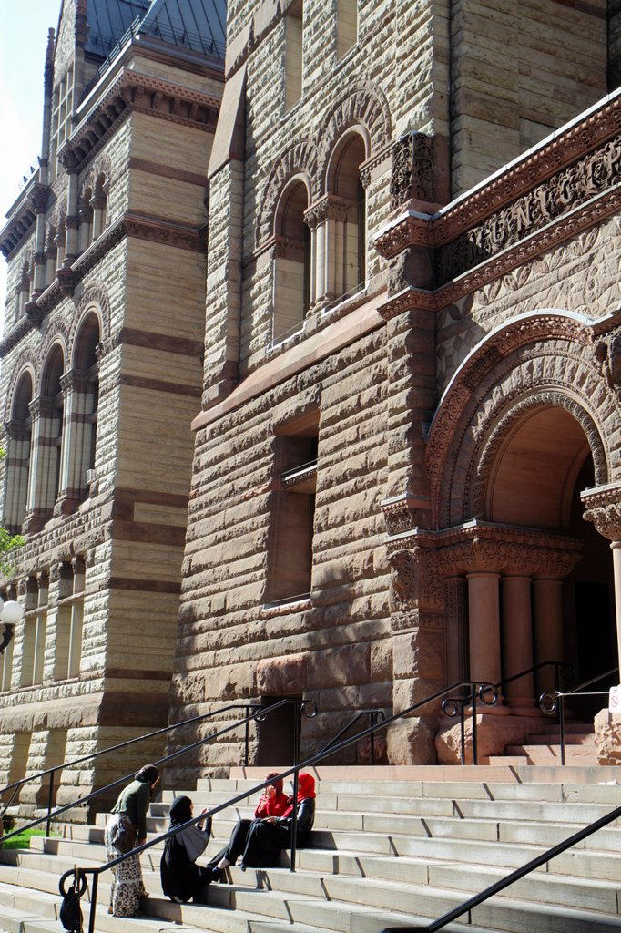 Canada, Ontario, Toronto, Queen Street West, Old City Hall, 1899, historic municipal building, landmark, National Historic Site, architect Edward Lennox, stairs, entrance, arch, stone, Muslim, woman, women, taking photo, : Stock Photo