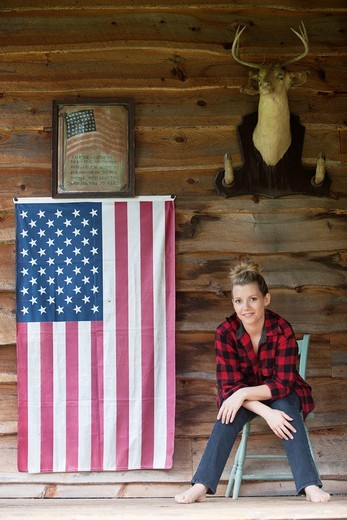 Woman sitting on front porch with flag and deer mount : Stock Photo