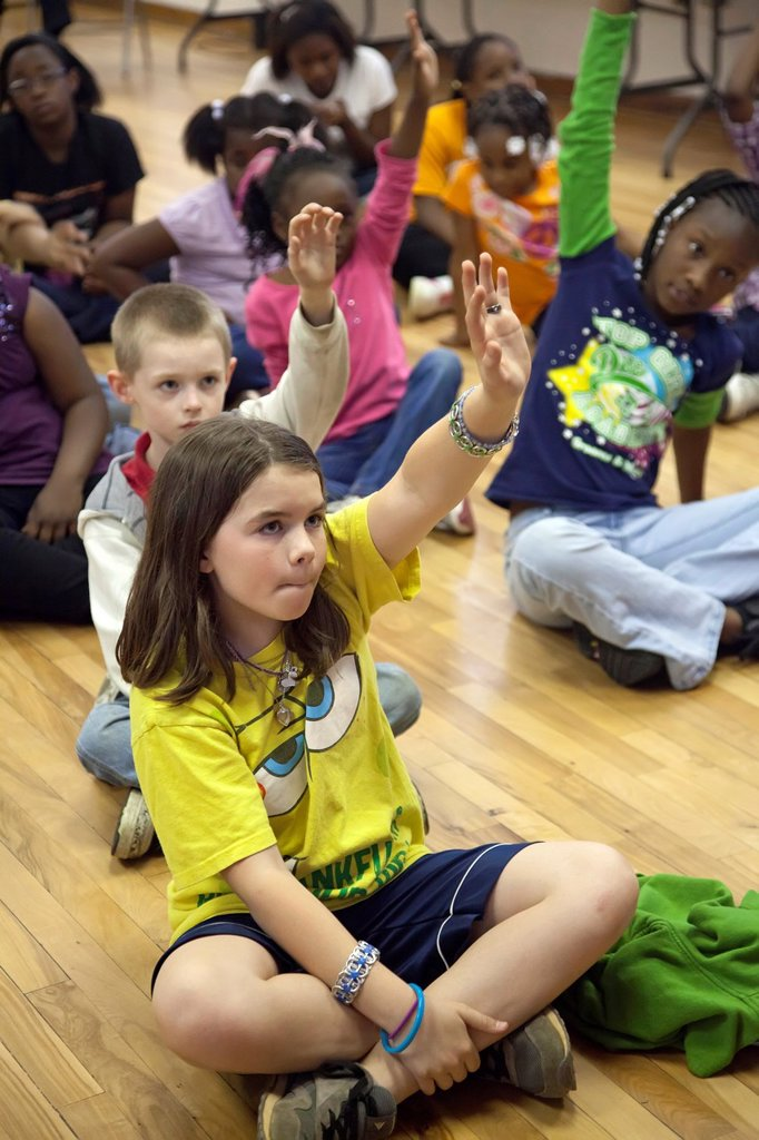 Stock Photo: 1566-930962 Knoxville, Tennessee - Children in the after-school program at Wesley House Community Center, a nonprofit supported by the United Methodist Church and the United Way  During time for devotions, children raised their hands to share what God means to them
