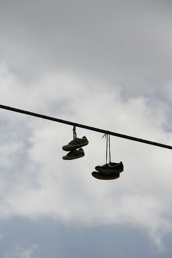 Stock Photo: 1566-931901 pairs of sports shoes hanging from power lines