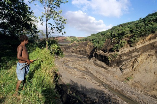 Young boy looking at the gully done by the water of the former siwi lake, Sulphur Bay, Tanna Island, Vanuatu : Stock Photo