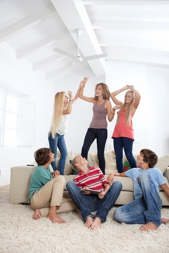 Group of teenagers dancing to music on a tablet : Stock Photo