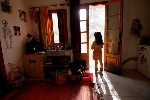 Stock Photo: 1566-935528 Young girl standing by the door in her house, Ibiza, Spain