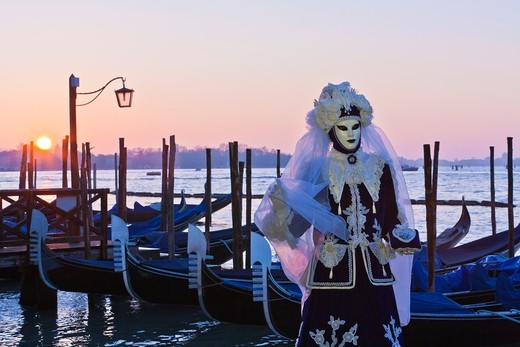 Stock Photo: 1566-948700 A masked woman at the carnival in Venice with gondolas in the background, Italy, Europe