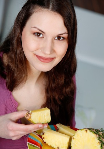 woman eating pineapple : Stock Photo