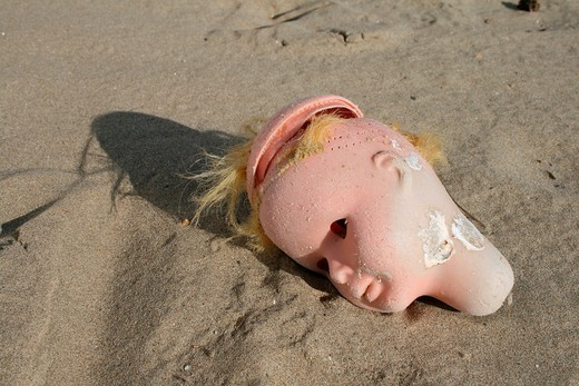 doll´s head washed up on beach : Stock Photo