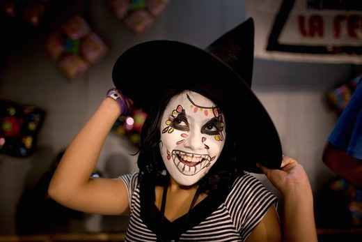 Stock Photo: 1566-949578 A girl with her face painted and a witch hat smiles and posses during the 16th International Clown Convention: The Laughter Fair organized by the Latino Clown Brotherhood, in Mexico City, October 17, 2011