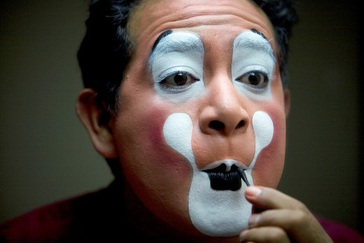 Stock Photo: 1566-949581 A clown puts on his make-up in front of a mirror in his hotel room before attending the 16th International Clown Convention: The Laughter Fair organized by the Latino Clown Brotherhood, in Mexico City, October 17, 2011