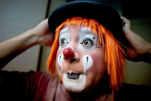 Stock Photo: 1566-949583 A clown puts on his bowler hat hat as he makes up in his hotel room before attending the 16th International Clown Convention: The Laughter Fair organized by the Latino Clown Brotherhood, in Mexico City, October 19, 2011