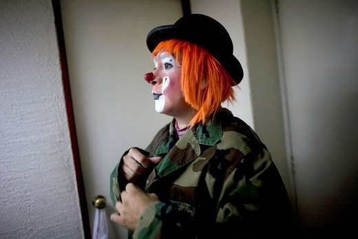 A clown puts on a military jacket as he makes up in his hotel room before attending the 16th International Clown Convention: The Laughter Fair organized by the Latino Clown Broterhood, in Mexico City, October 17, 2011 : Stock Photo