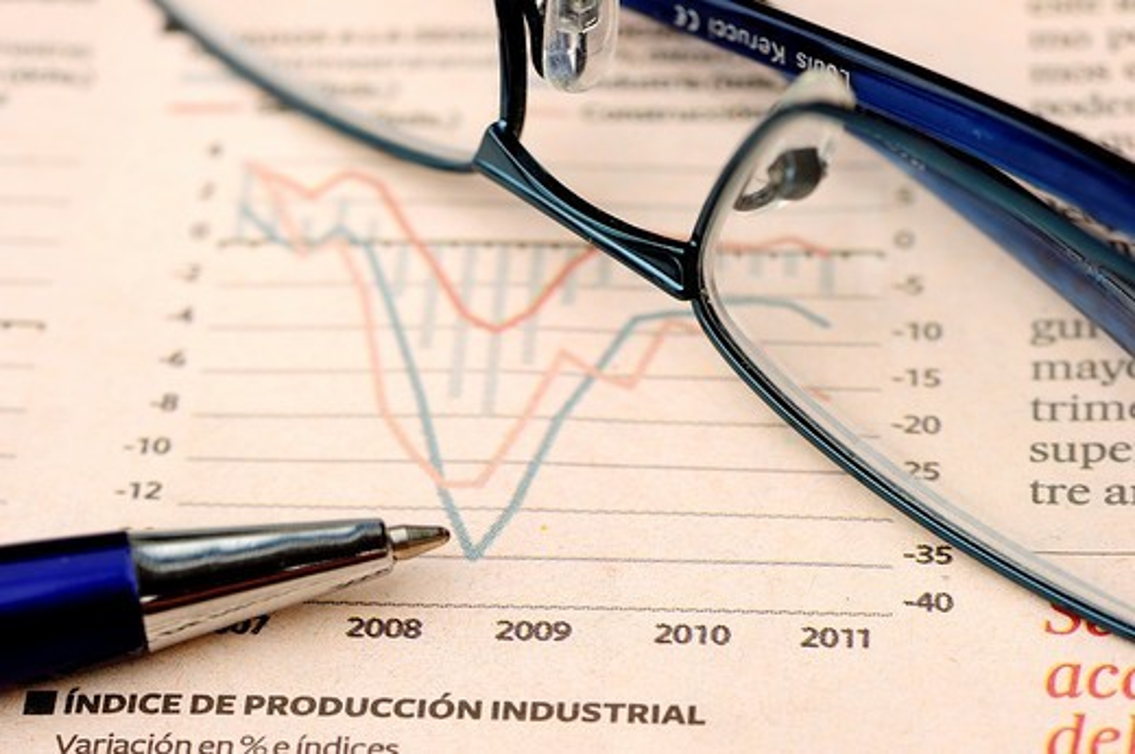 Glasses and pen on economic report : Stock Photo