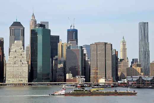 A view of Lower Manhattan and a barge in the East River  New York City, New York, United States : Stock Photo