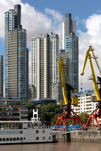 Stock Photo: 1566-958561 Highrise residential apartment buildings at the waterfront of the harbor, docklands, at a sunny day, blue sky, with a crane in the foreground, Buenos Aires, Argentina, South America