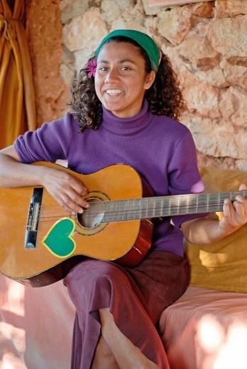 Attractive young brazilian woman plays the guitar at Greenheart´s La Casita Verde, Ibiza : Stock Photo