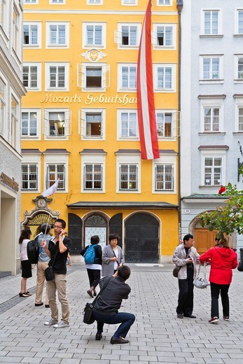Several tourists taking photos of the house where Wolfgang Amadeus Mozart was born in the Getreidegasse, Salzburg, Austria, Europe : Stock Photo