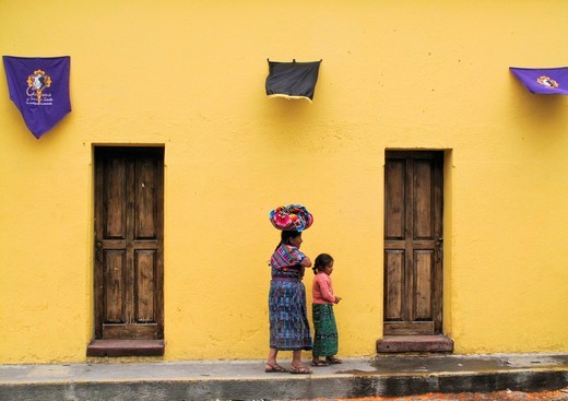 Maya mother and daughter walking on cobblestone street during Easter Week : Stock Photo