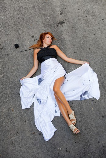 Stock Photo: 1566-965369 pretty young woman is laid-down on the road, spreading White long dress