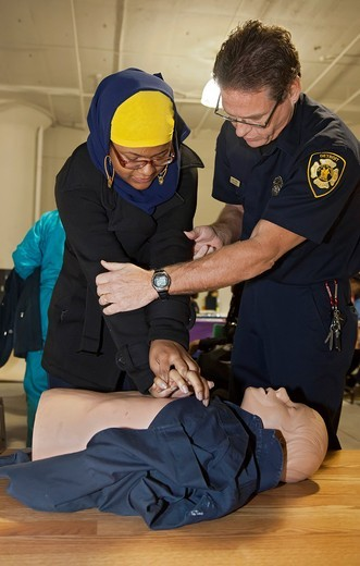 Stock Photo: 1566-966678 Detroit, Michigan - An emergency medical technician teaches cardiopulmonary resuscitation CPR to a person attending a community health fair